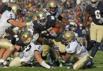 SOUTH BEND, IN - OCTOBER 29:  Jonas Gray #25 of the Notre Dame Fighting Irish is hit by (L-R) Caleb King #57, Chris Ferguson #23 and Wave Ryder #8 of the Navy Midshipmen at Notre Dame Stadium on October 29, 2011 in South Bend, Indiana. Notre Dame defeated