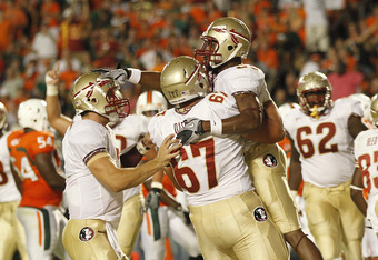 MIAMI, FL - OCTOBER 9: Jermaine Thomas #38 pats Christian Ponder #7 on the head as he is held by Andrew Datko #67 of the Florida State Seminoles after scoring a touchdown against the Miami Hurricanes on October 9, 2010 at Sun Life Stadium in Miami, Florid