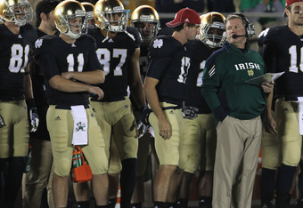 SOUTH BEND, IN - OCTOBER 22:  Head coach Brian Kelly of the Notre Dame Fighting Irish looks at Tommy Rees #11 during a game against the University of Southern California Trojans at Notre Dame Stadium on October 22, 2011 in South Bend, Indiana. USC defeate
