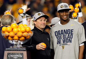 MIAMI GARDENS, FL - JANUARY 04:  (L-R) Head coach Dana Holgorsen and Geno Smith #12 of the West Virginia Mountaineers celebrate after they won 70-33 against the Clemson Tigers during the Discover Orange Bowl at Sun Life Stadium on January 4, 2012 in Miami