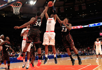 NEW YORK, NY - MARCH 09: Fab Melo #51 of the Syracuse Orange grabs a rebound against Yancy Gates #34 and Sean Kilpatrick #23 of the Cincinnati Bearcats during the semifinals of the Big East men's basketball tournament at Madison Square Garden on March 9,