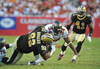 TAMPA, FL - OCTOBER 16:  Defensive tackle Shaun Rogers #92 of the New Orleans Saints tackles running back Earnest Graham #34 of the Tampa Bay Buccaneers October 16, 2011 at Raymond James Stadium in Tampa, Florida. (Photo by Al Messerschmidt/Getty Images)