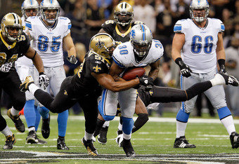 NEW ORLEANS, LA - JANUARY 07:  Jonathan Vilma #51 of the New Orleans Saints tries to tackle  Kevin Smith #30 of the Detroit Lions during their 2012 NFC Wild Card Playoff game at Mercedes-Benz Superdome on January 7, 2012 in New Orleans, Louisiana.  (Photo
