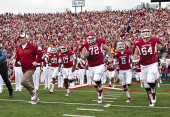 LITTLE ROCK, AR - NOVEMBER 19:   Head Coach Bobby Petrino and the Arkansas Razorbacks run onto the field before a game against the Mississippi State Bulldogs at War Memorial Stadium on November 19, 2011 in Little Rock, Arkansas. The Razorbacks defeated th