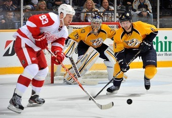 NASHVILLE, TN - DECEMBER 15:  Pekka Rinne #35 and Kevin Klein #8 of the Nashville Predators watch Johan Franzen #93 of the Detroit Red Wings pass the puck at the Bridgestone Arena on December 15, 2011 in Nashville, Tennessee.  (Photo by Frederick Breedon/
