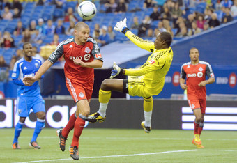 MONTREAL, CANADA - APRIL 7:  Donovan Ricketts #1 of the Montreal Impact stops the ball on an attempt by Danny Koevermans #14 of the Toronto FC during the MLS match at the Olympic Stadium on April 7, 2012 in Montreal, Quebec, Canada.  (Photo by Richard Wol