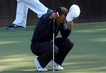 AUGUSTA, GA - APRIL 06:  Tiger Woods of the United States reacts after missing a putt on the 11th hole as his caddie Joe LaCava looks on during the second round of the 2012 Masters Tournament at Augusta National Golf Club on April 6, 2012 in Augusta, Geor