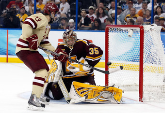 TAMPA, FL - APRIL 05:  Goalie Kent Patterson #35 of the Minnesota Gophers deflects the puck as Johnny Gaudreau #13 of the Boston College Eagles shoots during the NCAA Division 1 Men's Hockey Championship Semifinal Game at the Tampa Bay Times Forum on Apri