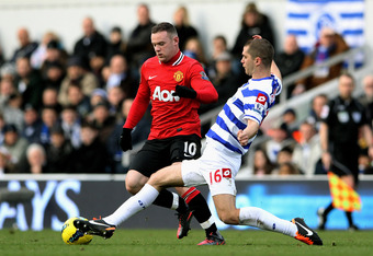 LONDON, ENGLAND - DECEMBER 18:  Wayne Rooney of Manchester United is tackled by Matthew Connolly of QPR during the Barclays Premier League match between Queens Park Rangers and Manchester United at Loftus Road on December 18, 2011 in London, England.  (Ph