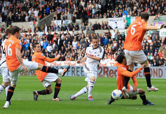 SWANSEA, UNITED KINGDOM - APRIL 06:  James Perch of Newcastle United runs into team mate Mike Williamson as they attempt to block the shot by Gylfi Sigurdsson of Swansea City during the Barclays Premier League match between Swansea City and Newcastle Unit