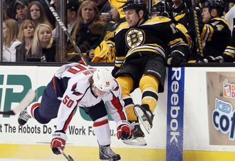 BOSTON, MA - MARCH 29:  Milan Lucic #17 of the Boston Bruins is hit by Cody Eakin #50 of the Washington Capitals on March 29, 2012 at TD Garden in Boston, Massachusetts.  (Photo by Elsa/Getty Images)