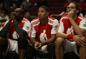CHICAGO, IL - DECEMBER 01: (L-R) Loul Deng #9, Derrick Rose #1 and Joakim Noah #13 of the Chicago Bulls watch their teammates during a loss to the Orlando Magic at the United Center on December 1, 2010 in Chicago, Illinois. The Magic defeated the Bulls 10