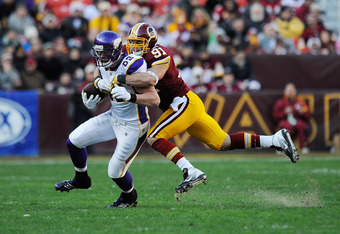 LANDOVER, MD - DECEMBER 24:  Kyle Rudolph #82 of the Minnesota Vikings is tackled by Ryan Kerrigan #91 of the Washington Redskins after catching a pass during the second quarter at FedExField on December 24, 2011 in Landover, Maryland.  (Photo by Patrick