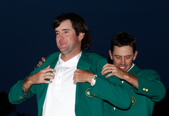 AUGUSTA, GA - APRIL 08:  Bubba Watson of the United States (L) is awarded the green jacket by Charl Schwartzel of South Africa (R) during the green jacket presentation after his one-stroke playoff victory during the 2012 Masters Tournament at Augusta Nati