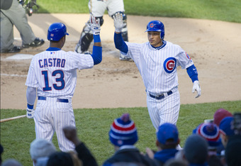 CHICAGO, IL - APRIL 9:   Starlin Castro #13 of the Chicago Cubs high-fives teammate Darwin Barney #15 after Barney hit a solo home run during the first inning against the Milwaukee Brewers at Wrigley Field on April 9, 2012 in Chicago, Illinois.  (Photo by