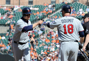 BALTIMORE, MD - APRIL 08: Justin Morneau #33 of the Minnesota Twins celebrates with Ryan Doumit #18 after scoring in the eighth inning against the Baltimore Orioles at Oriole Park at Camden Yards on April 8, 2012 in Baltimore, Maryland. (Photo by Greg Fiu