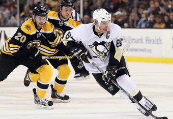 BOSTON, MA - APRIL 03:  Sidney Crosby #87 of the Pittsburgh Penguins takes the puck as Daniel Paille #20 of the Boston Bruins defends on April 3, 2012 at TD Garden in Boston, Massachusetts.  (Photo by Elsa/Getty Images)