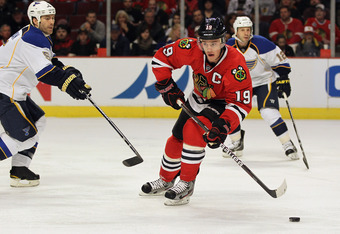 CHICAGO, IL - FEBRUARY 19: Jonathan Toews #19 of the Chicago Blackhawks moves between Barret Jackman #5 and Scott Nichol #12 of the St. Louis Blues at the United Center on February 19, 2012 in Chicago, Illinois. The Blackhawks defeated the Blues 3-1. (Pho