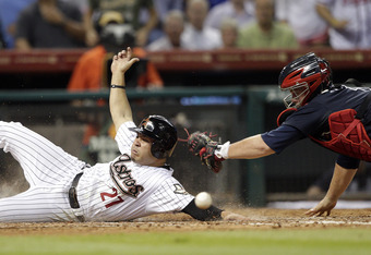 HOUSTON - APRIL 09:  Jose Altuve #27 of the Houston Astros avoids the tag at home as catcher Brian McCann #16 of the Atlanta Braves can't handle the throw after a triple by Travis Buck in the third inning at Minute Maid Park on April 9, 2012 in Houston, T