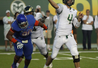 FORT COLLINS, CO - OCTOBER 15:  Quarterback Pete Thomas #4 of the Colorado State Rams delivers a pass as defensive lineman Billy Winn #90 of the Boise State Broncos cloeses in on the blind side at Sonny Lubick Field at Hughes Stadium on October 15, 2011 i
