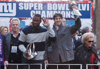 NEW YORK, NY - FEBRUARY 07:  (L to R) Co-owner of the New York Giants Steve Tisch, Justin Tuck #91 of the New York Giants, Quarterback Eli Manning #10 of the New York Giants and Ann Mara stand on a float during Giants' Victory Parade on February 7, 2012 i