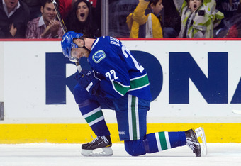 VANCOUVER, CANADA - JANUARY 31: Daniel Sedin #22 of the Vancouver Canucks celebrates with Sami Salo #6 after scoring a goal to defeat the Chicago Blackhawks 3-2 in overtime during NHL action on January 31, 2012 at Rogers Arena in Vancouver, British Columb