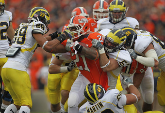 CHAMPAIGN, IL - NOVEMBER 12:  Jason Ford #21 of the Illinois Fighting Illini is tackled for a loss by (L-R) Troy Woolfolk #29, Desmond Morgan #44, Ryan Van Bergen #53, Craig Roh #88 and Mike Martin #68 of the Michigan Wolvories at Memorial Stadium on Nove