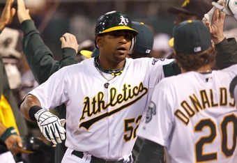 OAKLAND, CA - APRIL 07:  Yoenis Cespedes #52 of the Oakland Athletics is congratulated by teammates after hitting a three run home run against the Seattle Mariners during the seventh inning at O.co Coliseum on April 7, 2012 in Oakland, California. The Sea