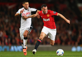 MANCHESTER, ENGLAND - MARCH 26:  Ryan Giggs of Manchester United holds off Clint Dempsey of Fulham during the Barclays Premier League match between Manchester United and Fulham at Old Trafford on March 26, 2012 in Manchester, England.  (Photo by Alex Live