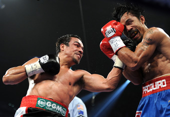 LAS VEGAS, NV - NOVEMBER 12:  (L-R) Juan Manuel Marquez throws a left to the face of Manny Pacquiao during the WBO world welterweight title fight at the MGM Grand Garden Arena on November 12, 2011 in Las Vegas, Nevada.  (Photo by Harry How/Getty Images)