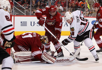 GLENDALE, AZ - FEBRUARY 11:  Goaltender Mike Smith #41 of the Phoenix Coyotes covers the puck as Jonathan Toews #19 of the Chicago Blackhawks skates in during the NHL game at Jobing.com Arena on February 11, 2012 in Glendale, Arizona.  The Coyotes defeate