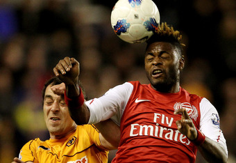 WOLVERHAMPTON, ENGLAND - APRIL 11:  Alex Song of Arsenal (R) beats Nenad Milijas in the air during the Barclays Premier League match between Wolverhampton Wanderers and Arsenal at Molineux on April 11, 2012 in Wolverhampton, England.  (Photo by Scott Heav