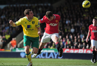 NORWICH, ENGLAND - FEBRUARY 26:  Grant Holt of Norwich City beats Jonny Evans of Manchester United to a header during the Barclays Premier League match between Norwich City and Manchester United at Carrow Road on February 26, 2012 in Norwich, England.  (P