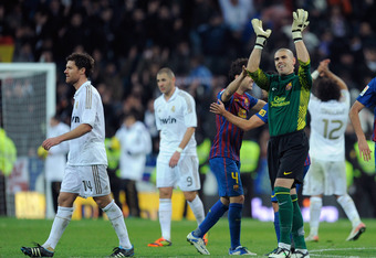 MADRID, SPAIN - DECEMBER 10:  Victor Valdes (R) of Barcelona celebrates beside Xabi Alonso of Real Madrid after Barcelona beat Real 3-1 in the La Liga match between Real Madrid and Barcelona at Estadio Santiago Bernabeu on December 10, 2011 in Madrid, Spa
