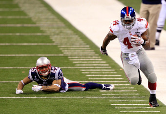 INDIANAPOLIS, IN - FEBRUARY 05:  Ahmad Bradshaw #44 of the New York Giants runs with the ball against Patrick Chung #25 of the New England Patriots during Super Bowl XLVI at Lucas Oil Stadium on February 5, 2012 in Indianapolis, Indiana.  (Photo by Chris
