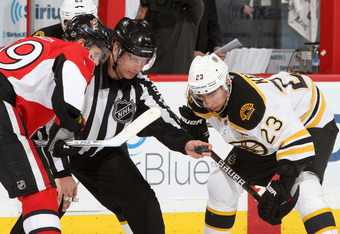 OTTAWA, CANADA - APRIL 5: Linesman Scott Cherrey #50 prepares to drop the puck for a faceoff between Jason Spezza #19 of the Ottawa Senators and Chris Kelly #23 of the Boston Bruins during an NHL game at Scotiabank Place on April 5, 2012 in Ottawa, Ontari