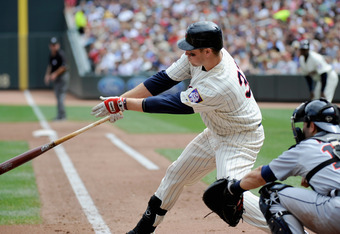 MINNEAPOLIS, MN - AUGUST 28: Justin Morneau #33 of the Minnesota Twins hits an RBI single as Alex Avila #13 of the Detroit Tigers catches in the third inning on August 28, 2011 at Target Field in Minneapolis, Minnesota. (Photo by Hannah Foslien/Getty Imag