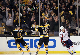 BOSTON, MA - APRIL 12:  Chris Kelly #23 of the Boston Bruins celebrates his game winning goal in overtime with Brian Rolston #12 as Dennis Wideman #6 of the Washington Capitals skates off in Game One of the Eastern Conference Quarterfinals during the 2012