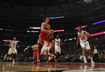 CHICAGO, IL - APRIL 02:  Goran Dragic #3 of the Houston Rockets goes up for a shot past Carlos Boozer #5 and Joakim Noah #13 of the Chicago Bulls at the United Center on April 2, 2012 in Chicago, Illinois. The Rockets defeated the Bulls 99-93. NOTE TO USE
