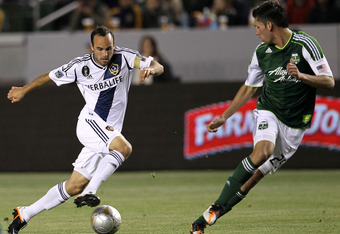 CARSON, CA - APRIL 14: Landon Donovan #10 of the Los Angeles Galaxy controls the ball against Steve Purdy #25 of the Portland Timbers at The Home Depot Center on April 14, 2012 in Carson, California.  The Galaxy won 3-1.  (Photo by Stephen Dunn/Getty Imag