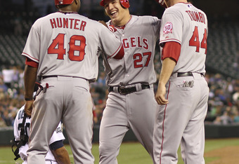 SEATTLE - AUGUST 30:  Mike Trout #27 of the Los Angeles Angels of Anaheim is congratulated by Torii Hunter #48 and Mark Trumbo #44 after hitting a three-run home run in the fourth inning against the Seattle Mariners at Safeco Field on August 30, 2011 in S