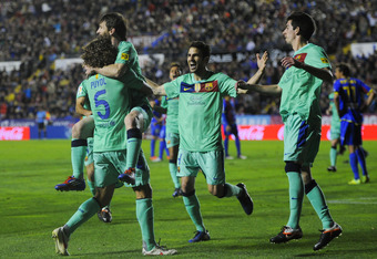 VALENCIA, SPAIN - APRIL 14:  Lionel Messi of FC Barcelona (2ndL) celebrates with his teammates after scoring his team's second goal during the La Liga match between Levante UD and FC Barcelona at Ciutat de Valencia on April 14, 2012 in Valencia, Spain. FC