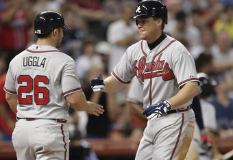 HOUSTON - APRIL 10:  Chipper Jones #10 of the Atlanta Braves receives congratulations from Dan Uggla #26 after hitting a two-run home run in the third inning against the Houston Astros at Minute Maid Park on April 10, 2012 in Houston, Texas.  (Photo by Bo