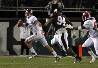 STARKVILLE, MS - NOVEMBER 12:  quarterback AJ McCarron #10 of the Alabama Crimson Tide scrambles away from pressure from defensive lineman Fletcher Cox #94 of the Mississippi State Bulldogs on November 12, 2011 at Davis Wade Stadium in Starkville, Mississ