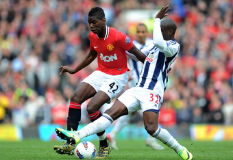 MANCHESTER, ENGLAND - MARCH 11:  Paul Pogba of Manchester United is challenged by Marc-Antoine Fortune of West Bromwich Albionduring the Barclays Premier League match between Manchester United and West Bromwich Albion at Old Trafford on March 11, 2012 in