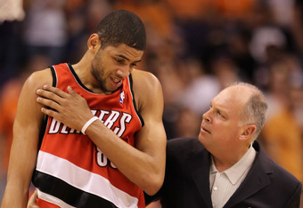 PHOENIX - APRIL 20:  Nicolas Batum #88 of the Portland Trail Blazers walks off the court with athletic trainer Jay Jensen after an injury during Game Two of the Western Conference Quarterfinals of the 2010 NBA Playoffs against the Phoenix Suns at US Airwa