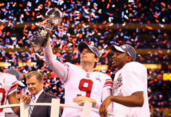 INDIANAPOLIS, IN - FEBRUARY 05:  Lawrence Tynes #9 and Hakeem Nicks #88 of the New York Giants celebrate with the VInce Lombardi trophy after the Giants won 21-17 against the New England Patriots during Super Bowl XLVI at Lucas Oil Stadium on February 5,