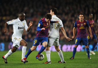 BARCELONA, SPAIN - JANUARY 25: Lionel Messi (L) of FC Barcelona tries to play the ball past Alvaro Arbeloa (R) of Real Madrid in between  during the Copa del Rey quarter final second leg match between Barcelona and Real Madrid at Camp Nou stadium on Janua
