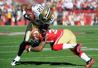 SAN FRANCISCO, CA - JANUARY 14:  Marques Colston #12 of the New Orleans Saints catches the ball for a first down against Dashon Goldson #38 of the San Francisco 49ers during the first quarter of the NFC Divisional playoff game at Candlestick Park on Janua