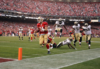 SAN FRANCISCO, CA - JANUARY 14:  Alex Smith #11 of the San Francisco 49ers runs in for a touchdown against the New Orleans Saints during the fourth quarter of their NFC Divisional playoff game at Candlestick Park on January 14, 2012 in San Francisco, Cali